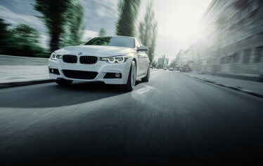 white bmw 3 series racing down street-paddock imports